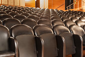 rows of black cozy chairs in a small theater