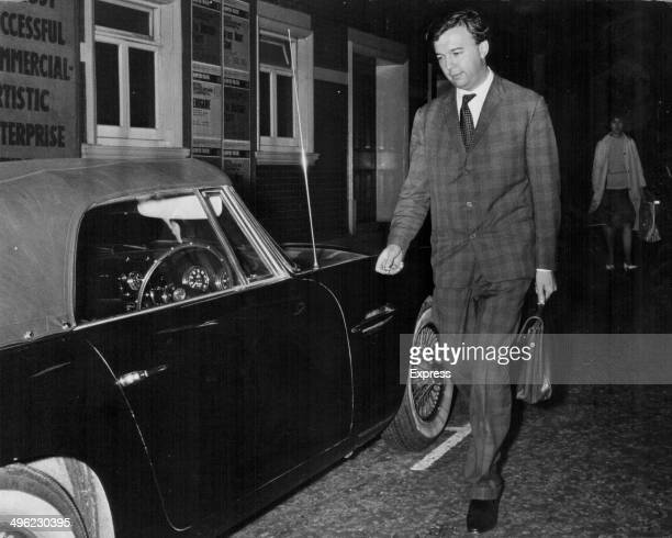 Theater director Peter Hall partner of actress Leslie Caron walking to his car in London June 24th 1964