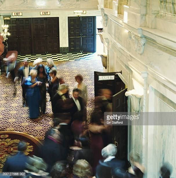 Theater goers in formal attire, entering auditorium, overhead view