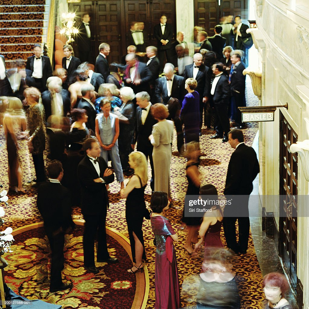 Theater goers in formal attire, waiting in lobby