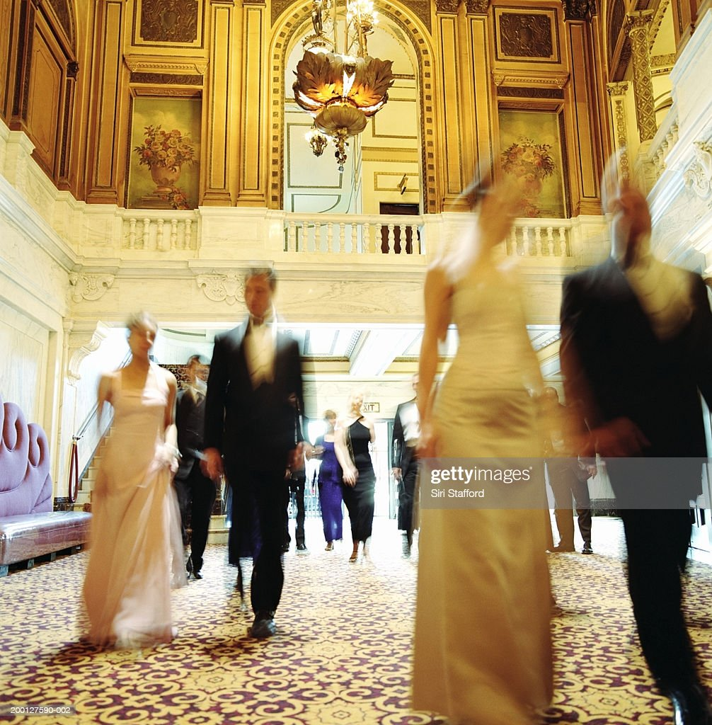 Theater goers in formal attire, walking through lobby, blurred motion : Stock Photo