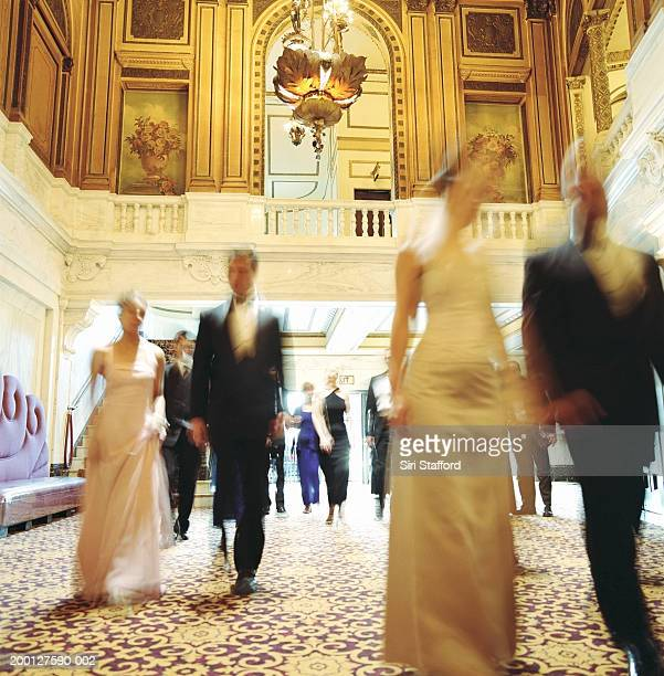 Theater goers in formal attire, walking through lobby, blurred motion