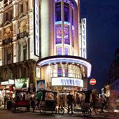 Theater on city street lit up at night