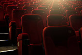 Red empty numbered theater/amphitheatre  seats with yellow backlight.