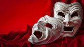 Theatre and opera concept with theatrical masks on red velvet. In Greek mythology Thalia was the Muse of comedy (laughing face), Melpomene was the Muse of tragedy (weeping face) with copy space