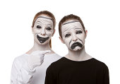 Two young teenage girls with their faces painted as the Theatre Masks.