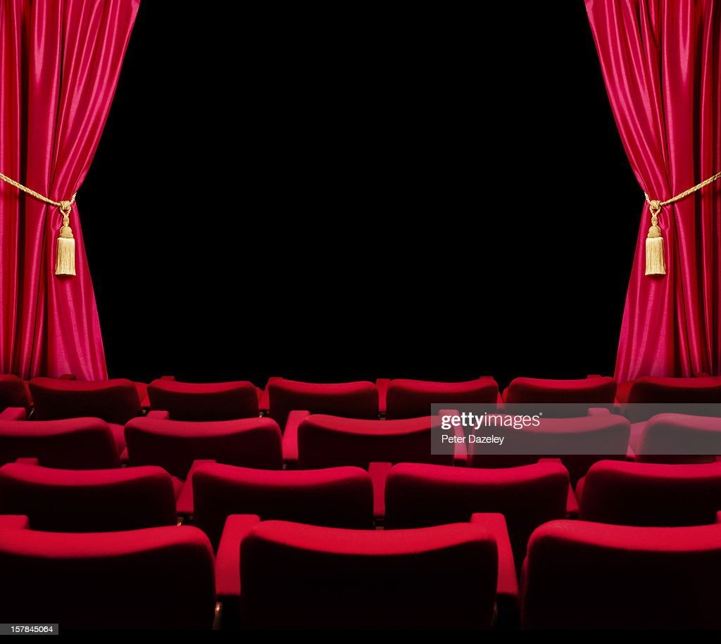 Theatre seats and open curtain to dark stage