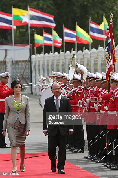 Thein Sein Myanmar's president right and Yingluck Shinawatra Thailand's prime minister left inspect a guard of honor at the Government House in...