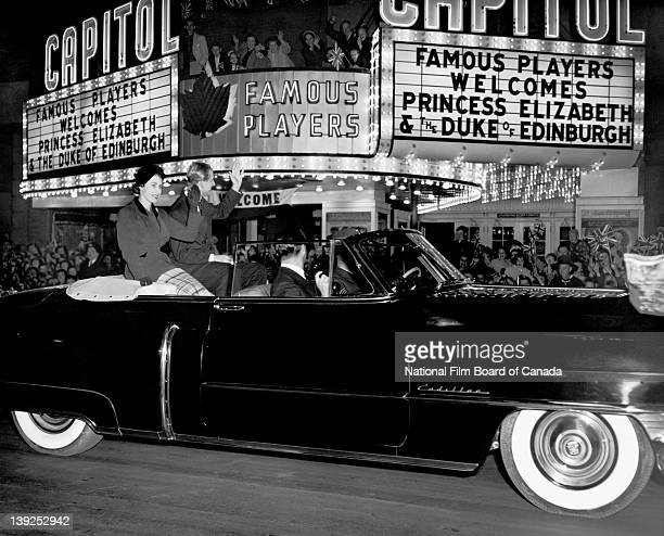 Their Royal Highnesses the Princess Elizabeth and Prince Philip Duke of Edinburgh riding in an open car wave at a cheering crowd gathered in front of...