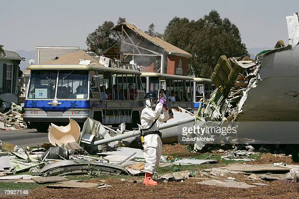 A theme park tourist bus passes as an FBI Hazardous Materials Team member in white and two members of the US Army Civil Support Team search for...