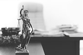 Themis statue on the table in lawyer's office in black and white.