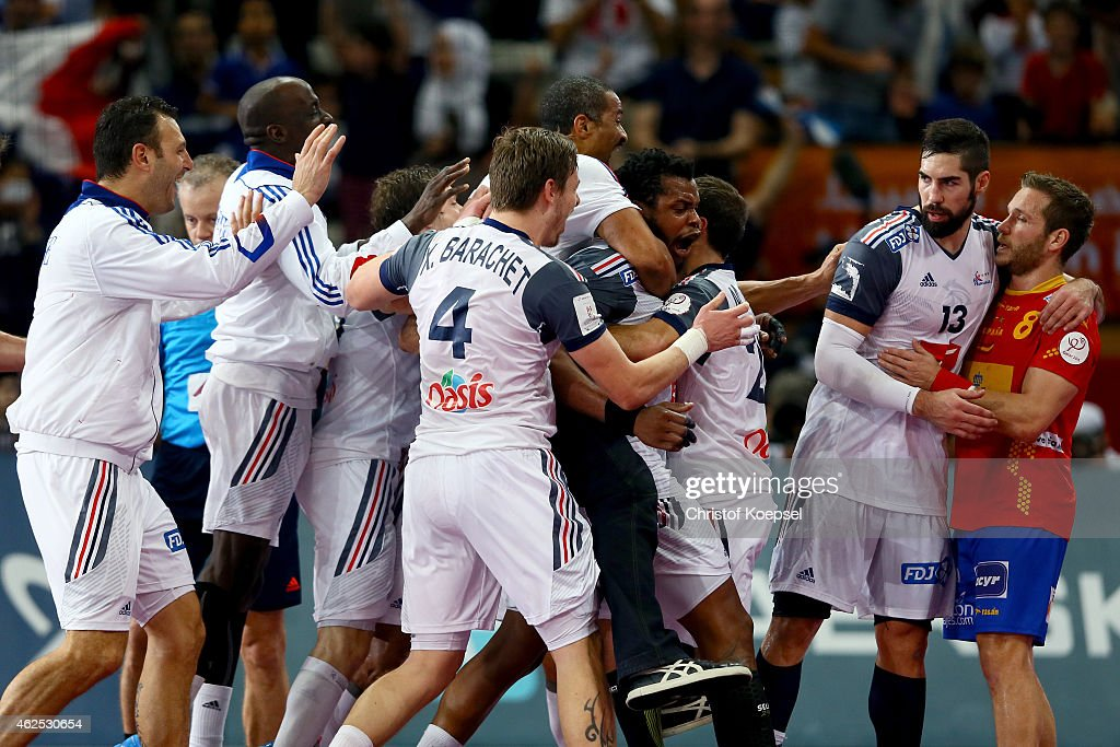 Then team of France celebrates after the semi final match between Spain and France at Lusail Multipurpose Hall and <a gi-track='captionPersonalityLinkClicked' href=/galleries/search?phrase=Nikola+Karabatic&family=editorial&specificpeople=620415 ng-click='$event.stopPropagation()'>Nikola Karabatic</a> of France (2nd R) comforts <a gi-track='captionPersonalityLinkClicked' href=/galleries/search?phrase=Victor+Tomas&family=editorial&specificpeople=3260334 ng-click='$event.stopPropagation()'>Victor Tomas</a> of Spain (R) after the Men's Handball World Championship on January 30, 2015 in Doha, Qatar. The match between Spain and France ended 22-26.