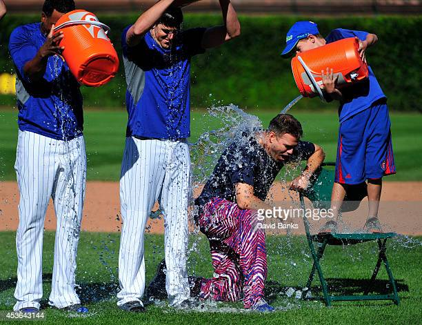 Theo Epstein President of Baseball Operations for the Chicago Cubs has ice water poured on him by nine year old Matthew Magner to raise money for ALS...