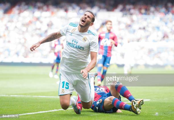Theo Hernandez of Real Madrid CF is tackled by Pedro Lopez of Levante UD during the La Liga match between Real Madrid and Levante at Estadio Santiago...