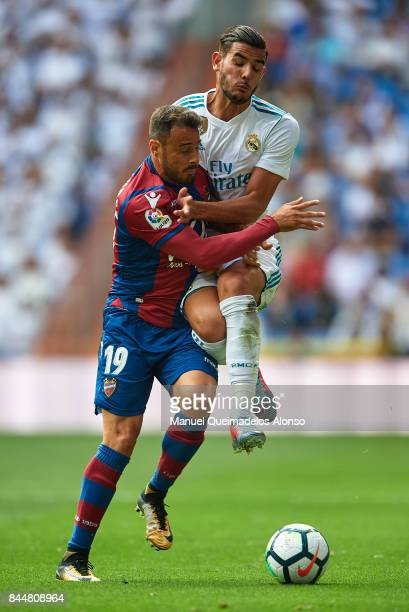 Theo Hernandez of Real Madrid competes for the ball with Pedro Lopez of Levante during the La Liga match between Real Madrid and Levante at Estadio...