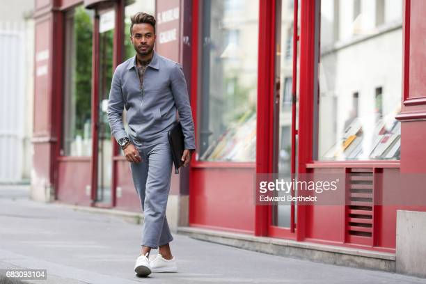 Theo Kimbaloula fashion blogger wears a Noyoco gray jacket Noyoco gray pants a Zara clutch and Agnes B sneakers and a tattoo representing a butterfly...