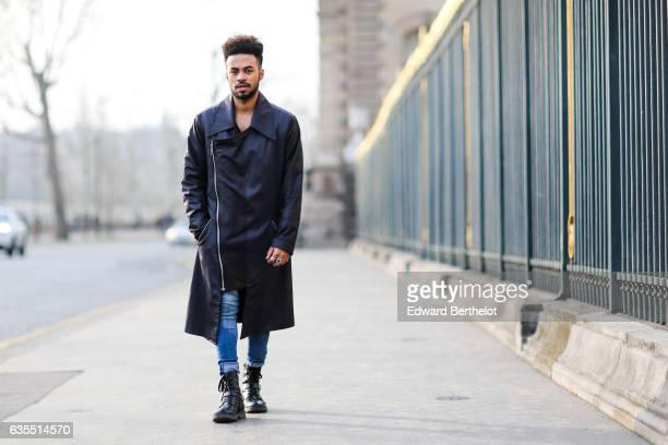 Theo Kimbaloula fashion blogger wears a Zwitter Paris black leather long coat Asos blue denim jeans and Asos boots on February 12 2017 in Paris France