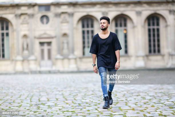 Theo Kimbaloula fashion blogger wears a Zwitter Paris black tshirt Asos blue denim jeans and Asos boots on February 12 2017 in Paris France