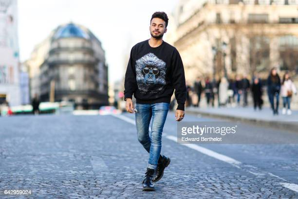 Theo Kimbaloula fashion blogger wears a Zwitter pull over with a printed logo representing a monkey with sunglasses Asos blue denim jeans pants and...