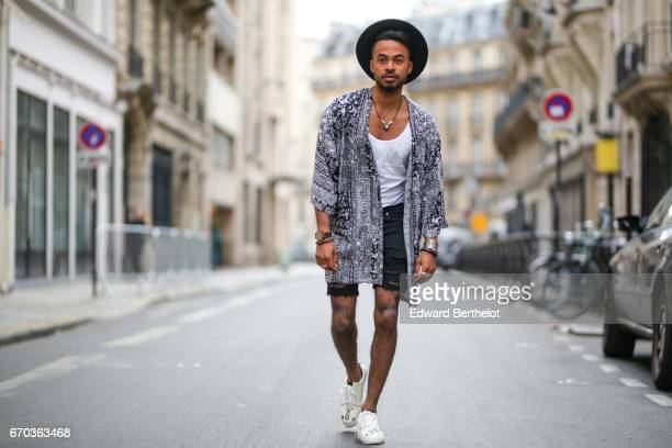 Theo Kimbaloula fashion blogger wears an Asos kimono an Asos tshirt an Asos hat a Zara short and Mr Monkie shoes on April 16 2017 in Paris France