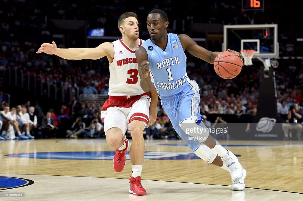 Theo Pinson of the North Carolina Tar Heels drives on Zak Showalter of the Wisconsin Badgers in the first half during the West Regional Semifinal of...