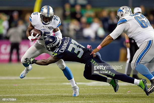 Theo Riddick of the Detroit Lions carries the ball as Kam Chancellor of the Seattle Seahawks attempts to make the tackle during the second half of...
