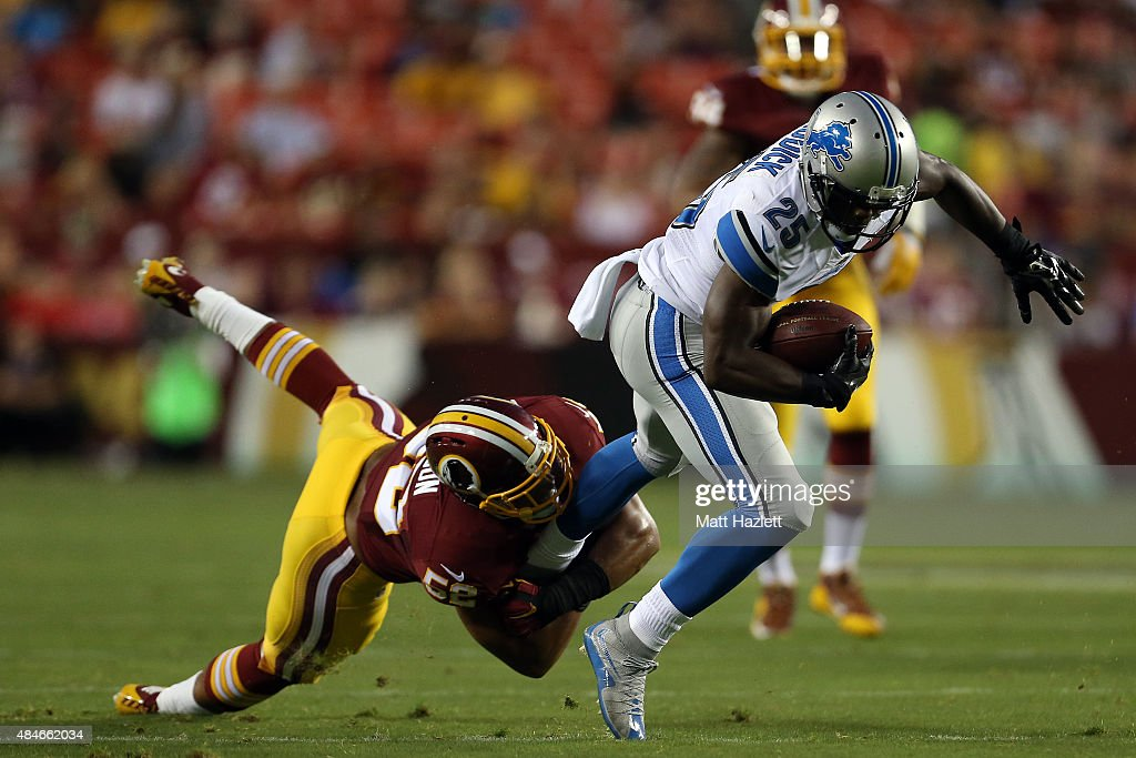 Theo Riddick #25 of the Detroit Lions is tackled by Keenan Robinson #52 of the Washington Redskins during a preseason game at FedEx Field on August 20, 2015 in Landover, Maryland.