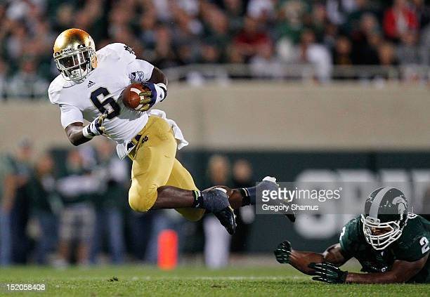 Theo Riddick of the Notre Dame Fighting Irish can't outrun the diving tackle of William Gholston of the Michigan State Spartans during a fourth...