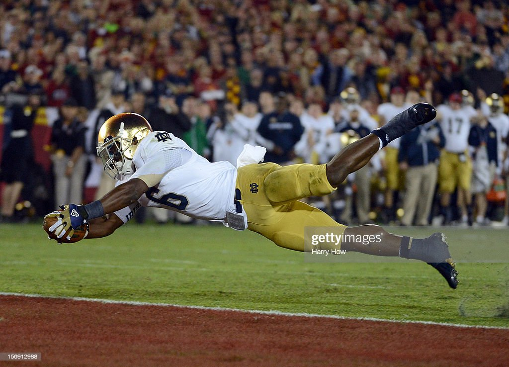 Theo Riddick #6 of the Notre Dame Fighting Irish dives across the goal line to score a touchdown to take a 10-0 lead over the USC Trojans at Los Angeles Memorial Coliseum on November 24, 2012 in Los Angeles, California.