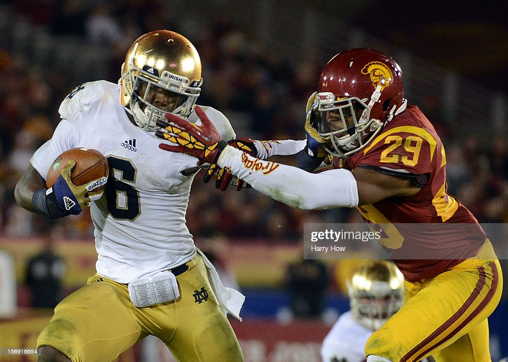 Theo Riddick #6 of the Notre Dame Fighting Irish gives Jawanza Starling #29 of the USC Trojans a stiff arm as he carries the ball during a 22-13 Notre Dame win at Los Angeles Memorial Coliseum on November 24, 2012 in Los Angeles, California.