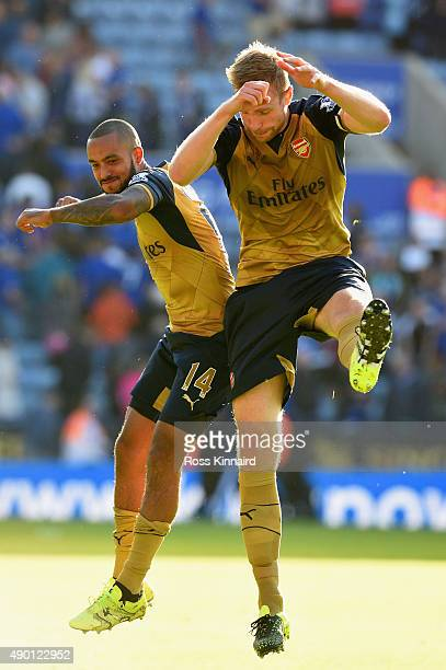 Theo Walcott and Per Mertesacker of Arsenal celebrate their team's 52 win in the Barclays Premier League match between Leicester City and Arsenal at...