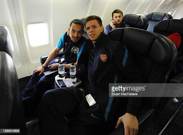 Theo Walcott and Wojciech Szczesny of Arsenal pose on the plane at Luton Airport as they travel to Milan ahead of their UEFA Champions League Group...