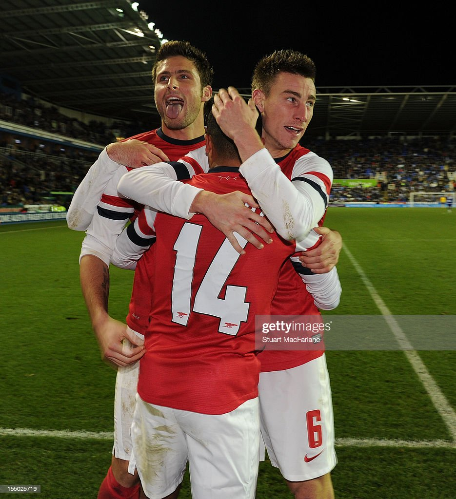 Theo Walcott #14 celebrates scoring the fourth Arsenal goal with Olivier Giroud (L) and Laurent Koscielny (R) during the Capital One Cup match between Arsenal and Reading at Madejski Stadium on October 30, 2012 in Reading, England.