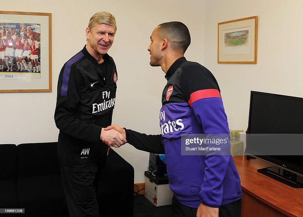 Theo Walcott is congratulated by Arsenal manager Arsene Wenger after signing a new contract at Arsenal Training Ground, London Colney on January 18, 2013 in St Albans, England.