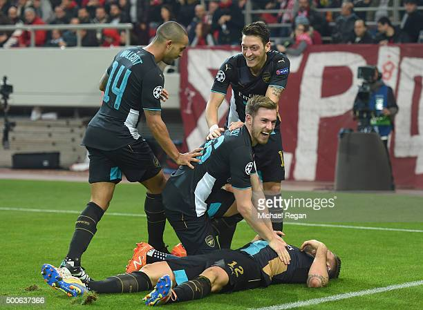 Theo Walcott Mesut Ozil and Aaron Ramsey congratulate Olivier Giroud of Arsenal after he scored the second goal for Arsenal during the UEFA Champions...