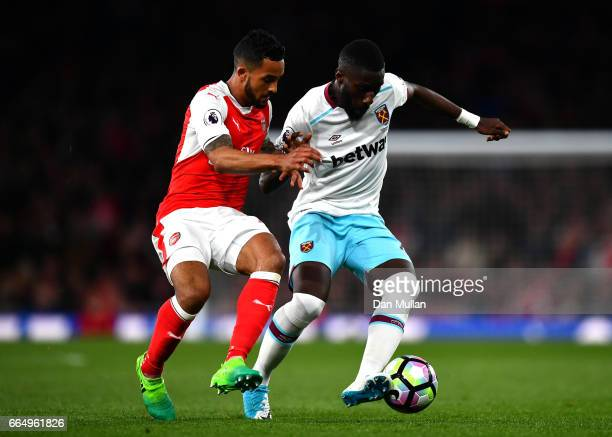 Theo Walcott of Arsenal and Arthur Masuaku of West Ham United battle for possession during the Premier League match between Arsenal and West Ham...