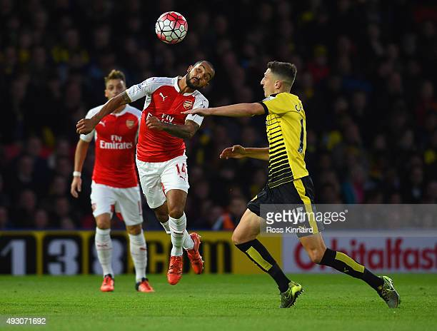 Theo Walcott of Arsenal and Craig Cathcart of Watford compete for the bal during the Barclays Premier League match between Watford and Arsenal at...