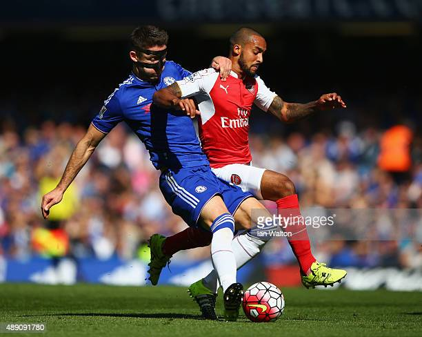 Theo Walcott of Arsenal and Gary Cahill of Chelsea compete for the ball during the Barclays Premier League match between Chelsea and Arsenal at...
