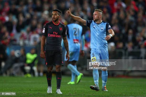 Theo Walcott of Arsenal and Jordy Buijs of Sydney FC react after the referee awards a penalty during the match between Sydney FC and Arsenal FC at...