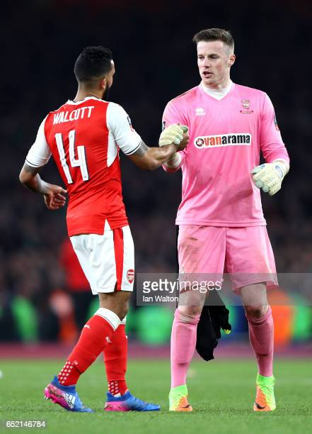 Theo Walcott of Arsenal and Paul Farman of Lincoln City embrace after The Emirates FA Cup QuarterFinal match between Arsenal and Lincoln City at...