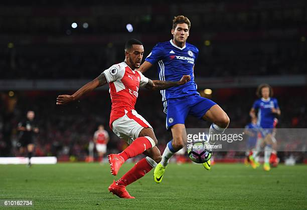 Theo Walcott of Arsenal attempts a cross while under pressure from Marcos Alonso of Chelsea during the Premier League match between Arsenal and...