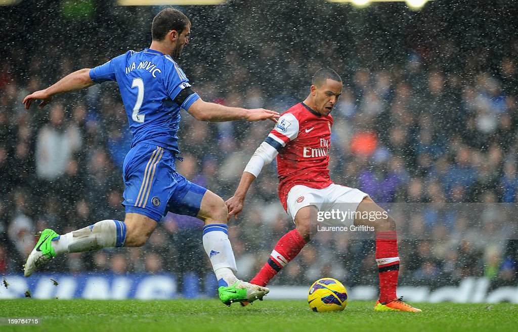Theo Walcott of Arsenal beats Branislav Ivanovic to score their first goal during the Barclays Premier League match between Chelsea and Arsenal at Stamford Bridge on January 20, 2013 in London, England.