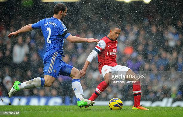 Theo Walcott of Arsenal beats Branislav Ivanovic to score their first goal during the Barclays Premier League match between Chelsea and Arsenal at...