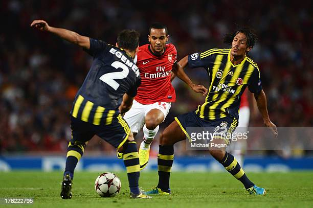 Theo Walcott of Arsenal breaks past Egemen Korkmaz and Bruno Alves of Fenerbahce during the UEFA Champions League Play Off Second leg match between...