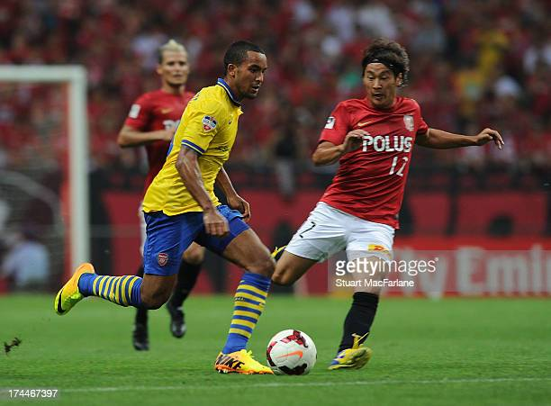 Theo Walcott of Arsenal breaks past Koji Node of Urawa during the preseason Asian Tour friendly match between Urawa Red Diamonds and Arsenal at...