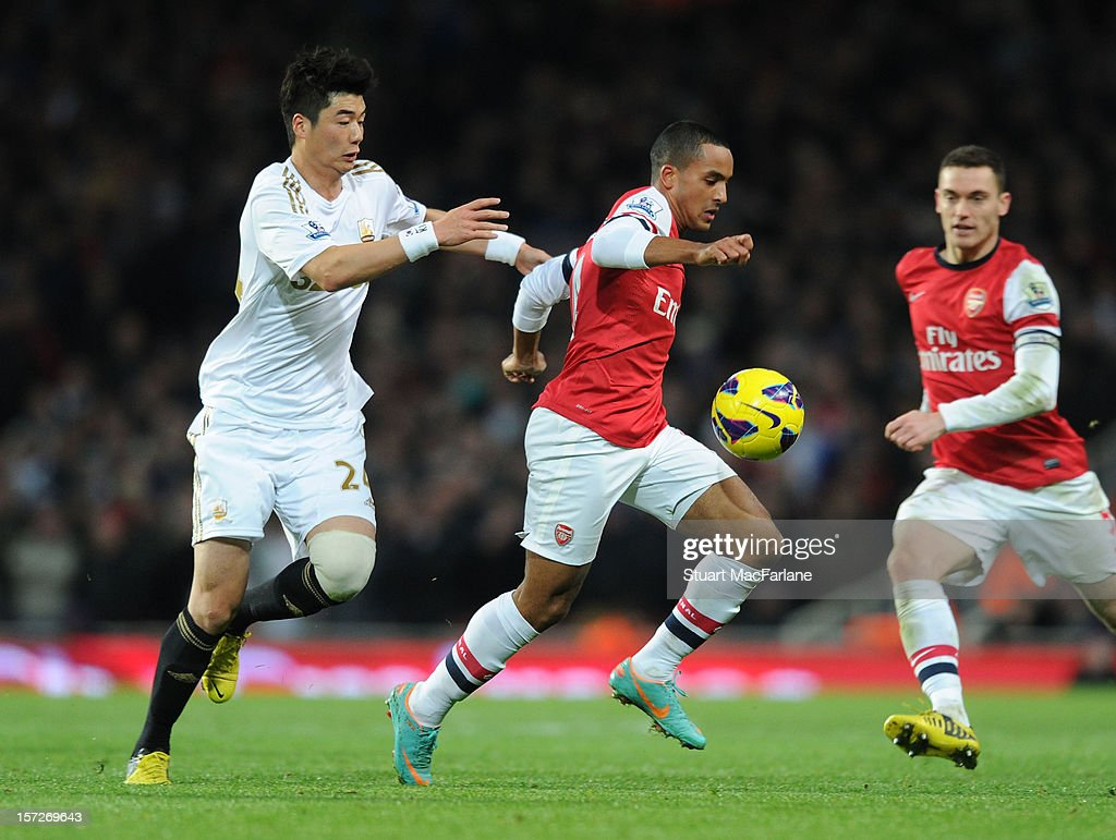 Theo Walcott of Arsenal breaks past Sung-Yueng Ki of Swansea during the Barclays Premier League match between Arsenal and Swansea City, at Emirates Stadium on December 01, 2012 in London, England.