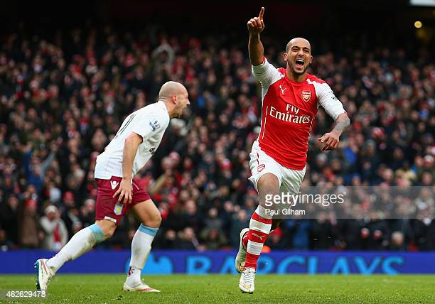 Theo Walcott of Arsenal celebrates after scoring his team's third goal during the Barclays Premier League match between Arsenal and Aston Villa at...