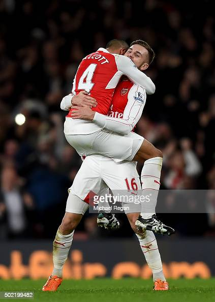 Theo Walcott of Arsenal celebrates scoring his side's first goal with Aaron Ramsey of Arsenal during the Barclays Premier League match between...