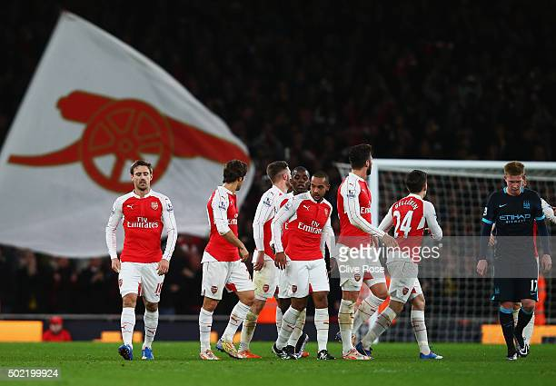 Theo Walcott of Arsenal celebrates scoring his team's first goal with team mates during the Barclays Premier League match between Arsenal and...