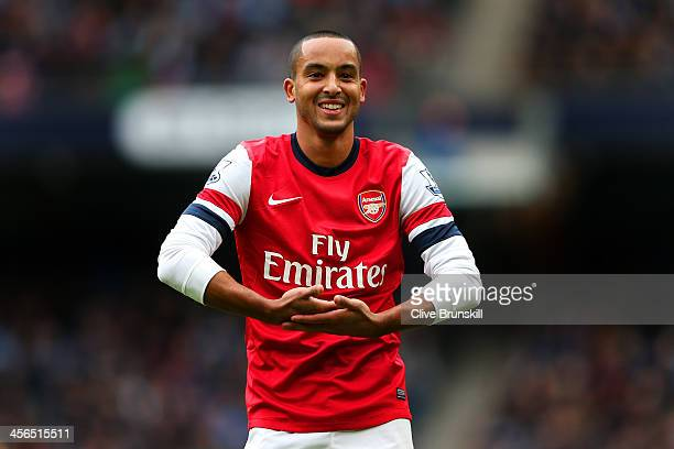Theo Walcott of Arsenal celebrates scoring their first goal during the Barclays Premier League match between Manchester City and Arsenal at Etihad...